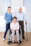 Caregiver with disabled senior couple Stock Images