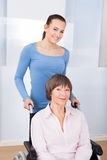 Caregiver With Disabled Senior Woman In Wheelchair Royalty Free Stock Photography