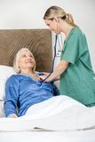 Caregiver Examining Senior Woman With Stethoscope Stock Photo