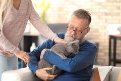 Caregiver giving cute cat to senior man. Caregiver giving cute cat to senior men at home royalty free stock photo