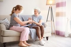 Caregiver giving glass of water to senior woman. Caregiver giving glass of water to senior women at home royalty free stock images