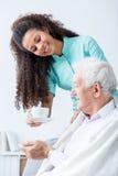 Caregiver giving senior man coffee. Caregiver giving senior men cup of coffee Royalty Free Stock Photos