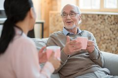 Caregiver and happy senior man sharing funny stories. Funny conversation. Cheerful merry senior men chatting with caregiver while enjoying tea and laughing royalty free stock photography