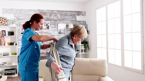 Caregiver helping elderly woman to get dressed