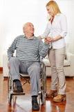 Caregiver helping senior citizen. Smiling caregiver helping senior citizen men in wheelchair standing up stock image