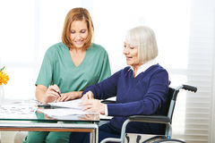 Caregiver helping senior woman with contracts Stock Image