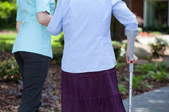 Caregiver helping woman with a crutch Stock Image