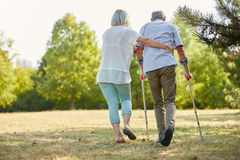 Caregiver helps man walking with crutches Royalty Free Stock Photography