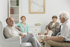 Caregiver and her wards. Young caregiver sitting with her elderly wards in nursing home Stock Photos