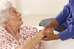 Caregiver holding elderly lady's hands cheerfully Stock Photo