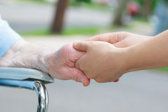 Caregiver holding elderly womans hand stock photography