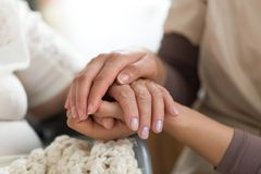Caregiver holding senior woman`s hands. Close-up photo of a female caregiver and senior women holding hands. Senior care concept royalty free stock images