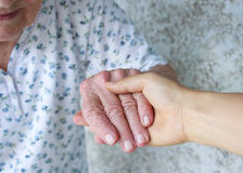 Caregiver holding seniors hand Stock Image