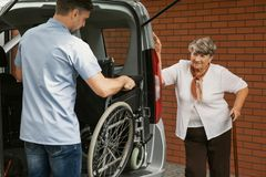 Caregiver holding wheelchair in the car stock photo