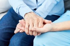 Caregiver holds comfortingly hand of an old woman. Caring nurse or geriatric nurse holds hand of an old woman Stock Photo