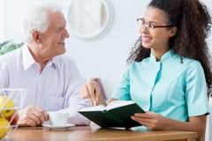 Caregiver keeping senior man company Royalty Free Stock Photography