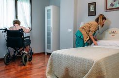 Caregiver making the bed of an elderly patient. In a nursing home royalty free stock images