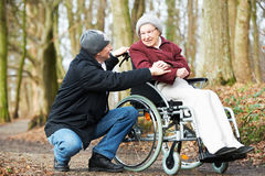 Caregiver man walking with disabled senior woman at wheelchair in nature Stock Photos