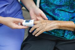 Caregiver monitoring oxygen saturation at fingertip of elderly. Woman stock photos