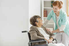 Caregiver in nursing home. Pretty young caregiver helping elderly disabled women in nursing home stock photography