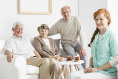 Caregiver and patients. Pretty young caregiver and her patients in nursing home royalty free stock image