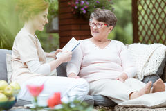 Caregiver reading journal. Young caregiver reading personal journal of lady with Alzheimer`s disease while sitting on garden sofa royalty free stock image