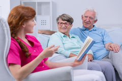 Caregiver reading to elderly couple Stock Image