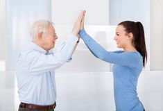 Caregiver and senior man giving high five Stock Images