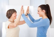 Caregiver and senior woman giving high five Royalty Free Stock Images