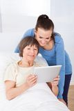 Caregiver and senior woman using digital tablet Stock Photography