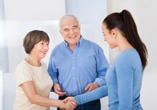 Caregiver shaking hands with senior couple Royalty Free Stock Photo