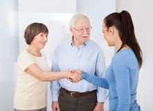 Caregiver shaking hands with senior couple Royalty Free Stock Images