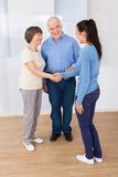 Caregiver shaking hands with senior couple Royalty Free Stock Photography