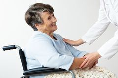 Caregiver supporting disabled senior woman in a wheelchair. Caregiver supporting happy disabled senior woman in a wheelchair stock photos