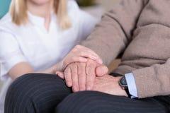 Caregiver supporting elder man Stock Image