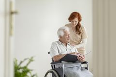 Caregiver supporting paralyzed elderly man in a wheelchair with. Caregiver supporting paralyzed elderly men in a wheelchair with photo album royalty free stock photos