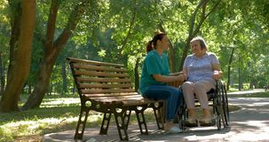 Caregiver talking to disabled senior woman in wheelchair outdoors stock video