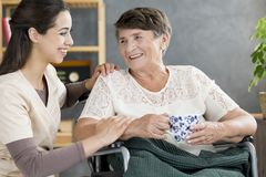 Caregiver talking to pensioner. Beautiful caregiver talking to a pensioner in a wheelchair while having a tea royalty free stock image