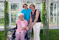 Caregivers for Elderly Patient at Home Garden. Royalty Free Stock Image