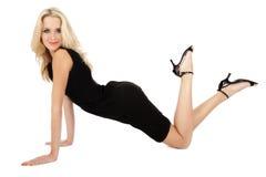 Careless. Beautiful slim blonde girl in black cocktail dress having fun stock image