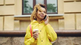 Careless African American girl is talking on cellphone and holding take-out coffee standing outdoors in modern city stock footage