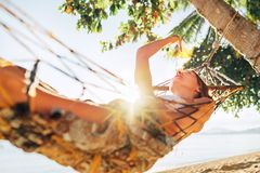 Careless blonde longhaired woman relaxing in hammock hinged between palm trees and playing with sun rays stock image