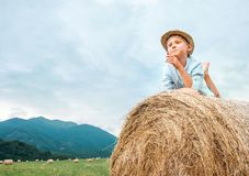 Careless boy lies on hay roll on the mountain field Royalty Free Stock Image