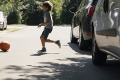 Careless boy running behind the ball on the road next to cars. Careless boy running behind the ball on the road next to the cars royalty free stock photos