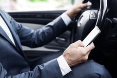 Careless bussinesman driving car and using mobile phone. Crop royalty free stock images