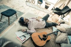 Careless dark-haired male musician resting in bedroom after repetition. Intense musical training. Careless dark-haired male musician resting in bedroom after royalty free stock photography