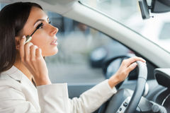 Careless driver. Side view of young woman in formalwear doing make-up while driving a car Royalty Free Stock Photos