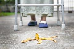 Careless elderly woman step over a banana peel. On walkway Stock Photography