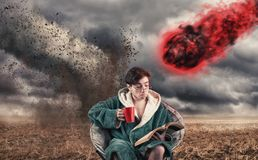 Careless man. Drinking coffee and reading a book while a tornado and a meteor coming to him stock photos