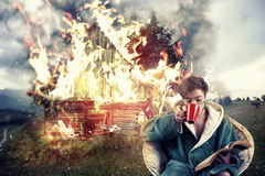 Careless man. Man drinks coffee and reading a book while his house is on fire, on a mountain background. Concept of a careless man royalty free stock photo